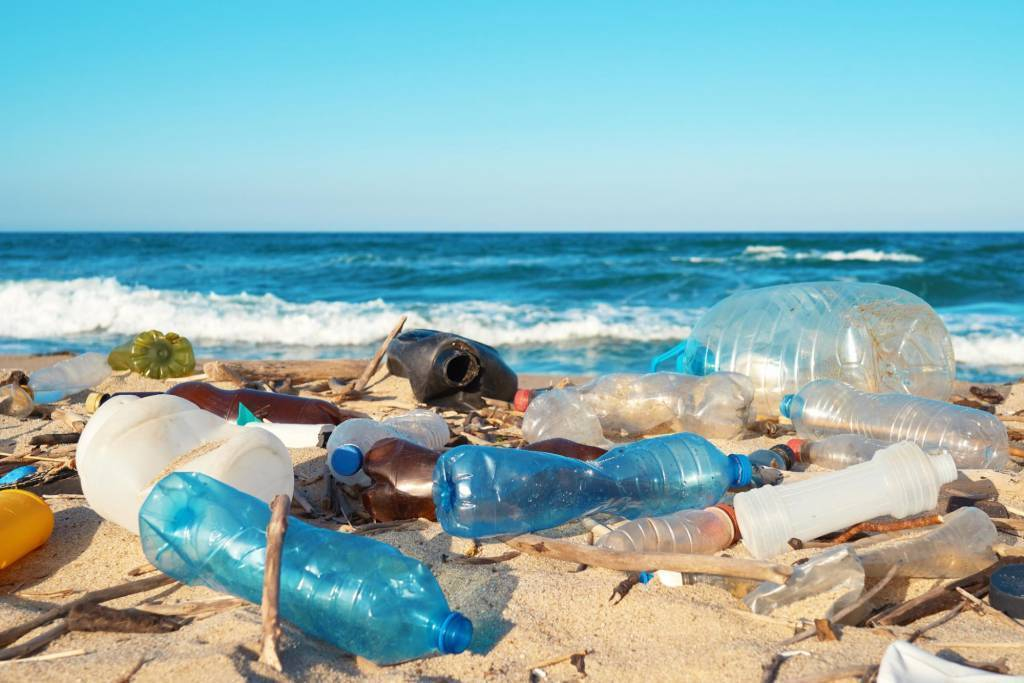ocean waste plastic packaging on a beach leading movement to circular economy trend